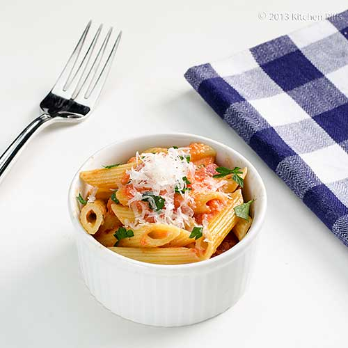 Penne alla Vodka in white ramekin, with fork and napkin in background