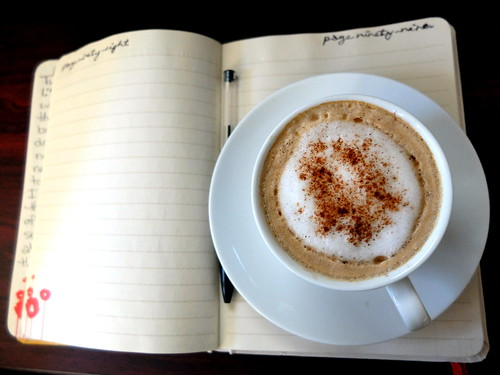 cappuccino, paper journal and a pen.
