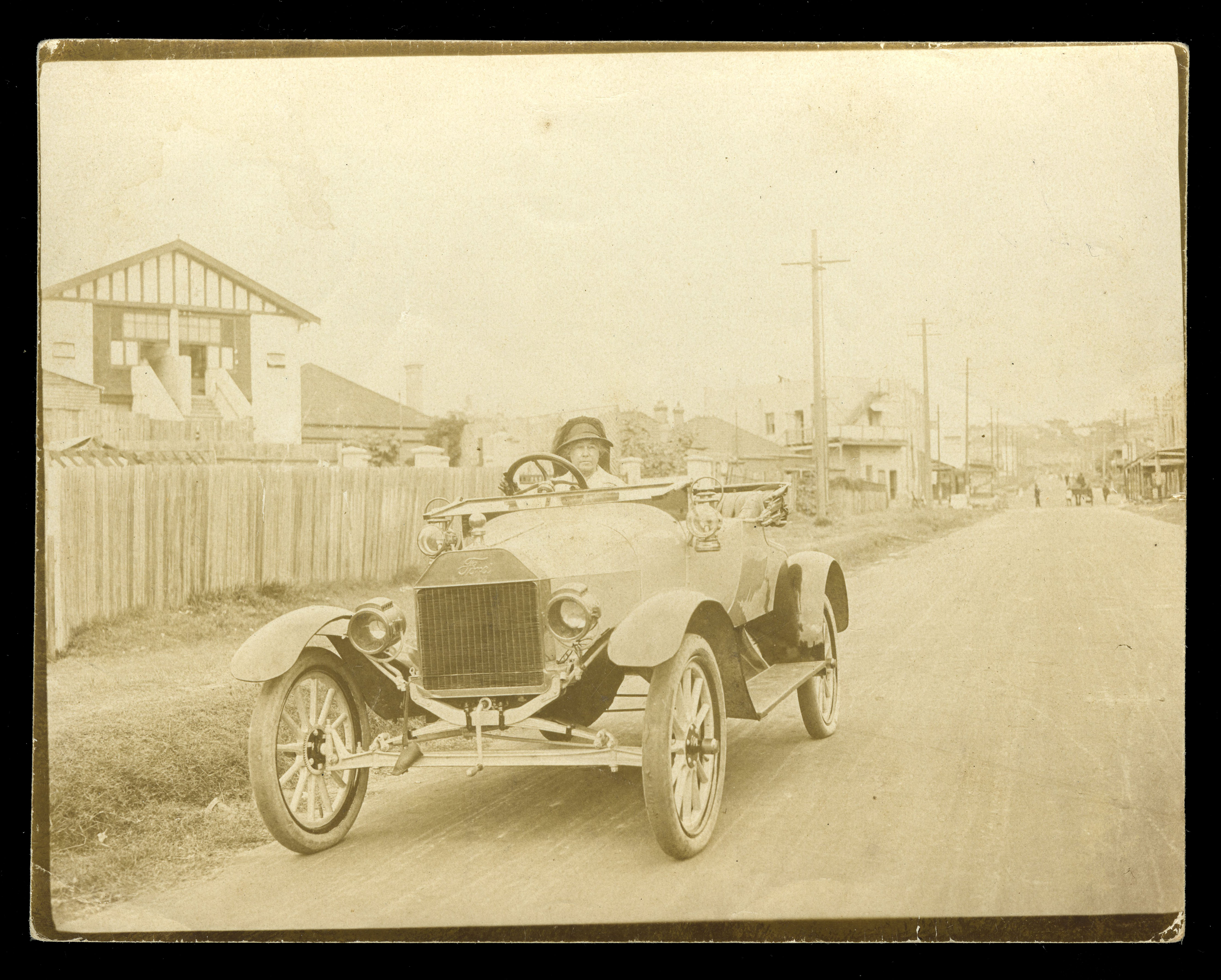 Photograph of an unidentified woman driving a car