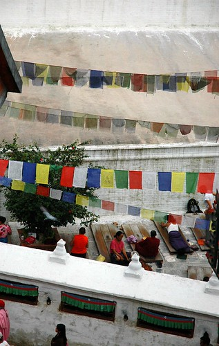 Prostrators on prostration boards, Tibetan prayer flags, inside Boudha Stupa, Boudhanath, Kathmandu, Nepal by Wonderlane