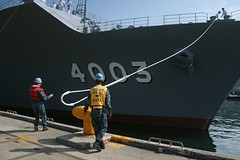 U.S. Navy Sailors assist as JS Kunisaki (LST 4003) departs Yokosuka for Pacific Partnership. (U.S. Navy/Lt. Jesus Uranga)