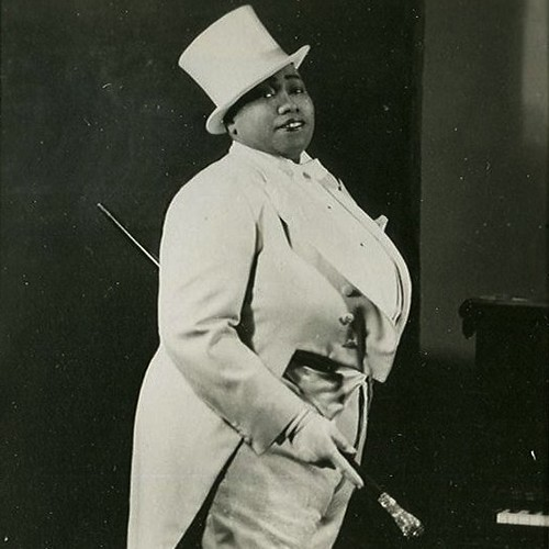Bentley, a large black woman, in a fancy white tuxedo and top hat