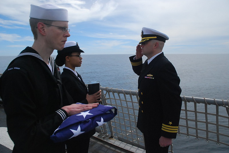 USS Shoup At Sea - Yeoman 3rd Class Andrea Burks and Operations Specialist 2nd Class Brian Hansen present ashes to USS SHOUP's Executive Officer, Commander Bryant Trost during a Burial at Sea Ceremony while off the coast of Southern California.