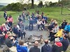 Group on team building event around campfire having a sing song
