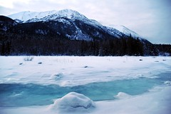 Sixmile River estuary slough, freshwater and seawater blend and make crackling sounds as the tide comes and goes, ice, snow, mountains, avalanche area, view to the west, Sunrise, Alaska, USA