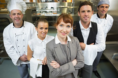 Nice female manager posing with the staff in a modern kitchen catering