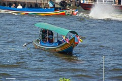 Dragon boat or Longtail boat on the Chao Phraya river seen from Wat Arun, Bangkok, Thailand