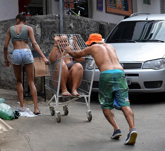 Momento surrealista en Rocinha con unos chicos subidos en un carro de la compra