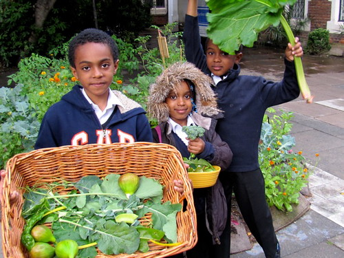 A little patch of ground, London. 3 children stand with their harvest of green leaves and figs. One has a rhubarb leaf sheltering his head