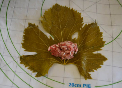 For the grape leaf rolls, place a small amount of the meat mixture onto the grape leaf.