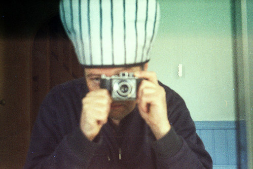 reflected self-portrait with Agfa Karat camera and stripy hat by pho-Tony