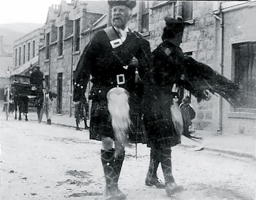 Two Highlanders Walking in Bridge Street, Ballater, Royal Deeside, Aberdeenshire, Scotland, UK. Date Unknown.