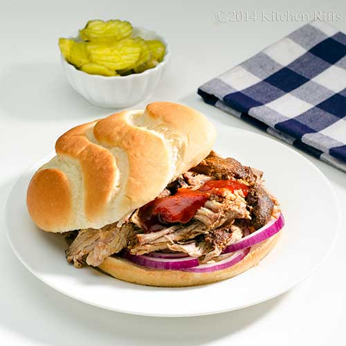 Oven Slow-Cooked BBQ Pulled Pork in sandwich with BBQ sauce and red onions
