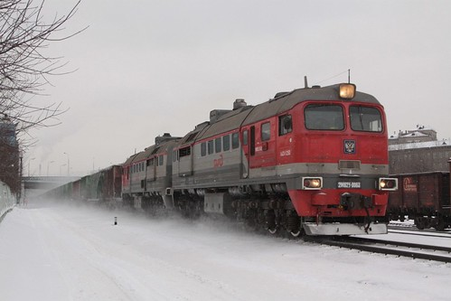 Diesel locomotive 2М62У-0063 kicks up snow while hauling mixed freight