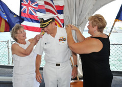 Rear Adm. Brian Antonio has his new shoulder boards placed on by his morhter Gloria Antonio, left, and his wife Kathy Sue during his promotion aboard the USS Missouri Memorial. (U.S. Navy Photo by Mass Communication Specialist 2nd Class David Kolmel)