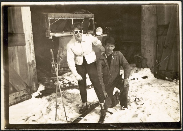 Woman with skis and stocks and man in front of a snowplough in shed, Snowy Mountains ski fields, New South Wales, ca. 1940.