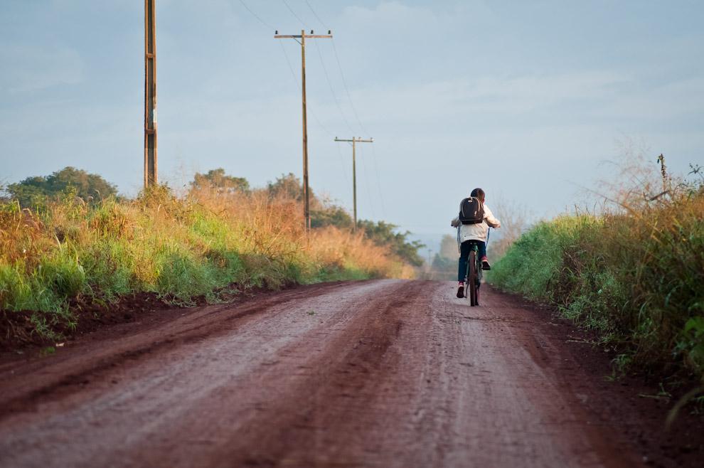 Un niño se dirige en bicicleta a su lejana escuela a las 7:00 de la mañana, lo vimos pasar mientras esperábamos la salida del sol en las afueras del pueblo de Itá Verá. (Elton Núñez)