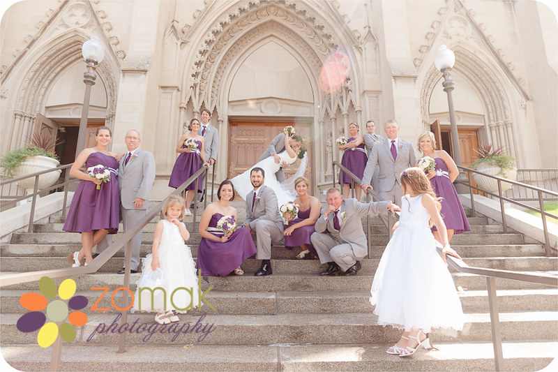 The groom dips his bride with wedding party on the stairs of st helena cathedral on their wedidng day