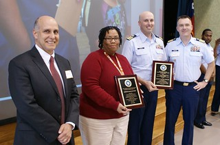 Coast Guard Cmdr. Ricardo Alonso, the commanding officer of Marine Safety Unit Texas City and Sharon Williams, the vice-principal of Kohfeldt Elementary School hold up their plaques, after the MSU Texas City unit and elementary school were honored as recipients of the 2013 Sustained Excellence in Coast Guard Partnership in Education Award, Jan. 29, 2014. The Coast Guard Partnership in Education Program began as a way to enhance educational opportunities and promote career awareness among the youth of the nation.