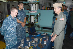 Machinery Repairman Joshua Carr, left, briefs the machine         shop's capabilities of the submarine tender USS Frank Cable (AS 40)         to Adm. Harry B. Harris Jr., commander of U.S. Pacific Fleet, during         a tour of the ship. While aboard, Harris toured the ship's repair,         health services, and operations divisions along with the pilot         house, allowing him the opportunity to meet and talk with Sailors         and civilian mariners.  (U.S. Navy photo by Mass Communication         Specialist 2nd Class Greg House)