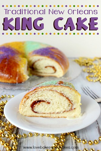 Traditional New Orleans King Cake on white plate with gold beaded necklace.
