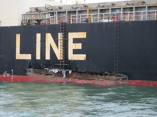 A Coast Guard small boat carrying marine inspectors and investigators from Coast Guard Marine Safety Unity Texas City get a closer look at the damage caused by a collision between this vessel, the cargo ship Genius Star VII and a barge carrying 840,000 gallons of fuel oil. There were no pollution or injuries associated with the collision. U.S. Coast Guard photo.