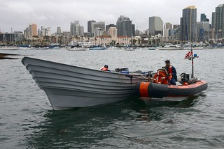 Crew members of U.S. Coast Guard Cutter Sea Otter tow a panga boat that was seized in a smuggling interdiction into San Diego Bay, Dec. 3, 2013. The crew of Coast Guard Cutter Active intercepted the panga with 5,000 pounds of marijuana and two suspects aboard approximately 140 miles southwest of San Diego. (U.S. Coast Guard photo by Petty Officer 1st Class Henry G. Dunphy)