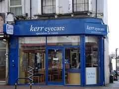 "A ground floor end-of-terrace shop with a fully glazed front and blue-painted surround.  The top of the frontage reads ""kerr eyecare / specialists in vision"" in lowercase white letters.  A sign in one of the windows reads ""Car Park to Rear""."