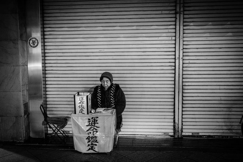 A lonely fortune teller waiting for customers in the night at Shinjuku.