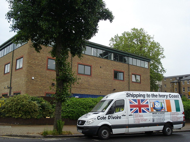 """A white van outside a boxy brick building with a row of windows around the top.  Writing on the van reads """"Shipping to the Ivory Coast""""."""