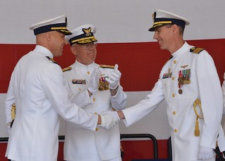 Cmdr. Andrew W. Eriks (left), commanding officer of Coast Guard Air Station/Sector Field Office Port Angeles, Wash., shakes hands with Capt. Keith P. McTigue (right) after relieving him as commanding officer during a change-of-command ceremony presided over by Rear Adm. Richard T. Gromlich (middle), commander of the 13th Coast Guard District, held at the air station, July 2, 2014. Eriks is the 40th commanding officer of Air Station/SFO Port Angeles, which logistically supports three small boat stations, five patrol boats and a medium endurance cutter. U.S. Coast Guard Photo by Petty Officer 3rd Class Amy Nuckolls.