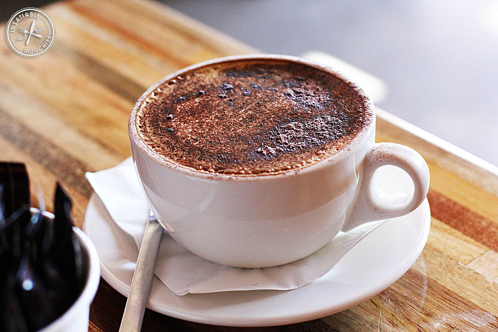 A mug of cappuccino is topped with thick frothy milk and a dusting of cocoa powder.