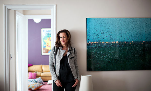 Kim France stands in front of a pastel wall