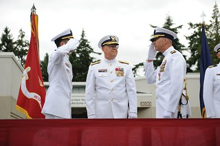 Cmdr. Michael L. Schoonover (left) and Cmdr. Thomas P. Sullivan (right) salute each other after Schoonover relieved Sullivan as commanding officer of Coast Guard Maritime Force Protection Unit Bangor, Wash., during a change of command ceremony presided over by Rear Adm. Richard T. Gromlich (middle), commander of the 13th Coast Guard District, held at Naval Base Kitsap in Silverdale, Wash., July 25, 2014. Sullivan retired following the ceremony after serving 33 years in the Coast Guard as both an enlisted electronics technician and a commissioned officer. (U.S. Coast Guard photo by Petty Officer 3rd Class Katelyn Shearer)