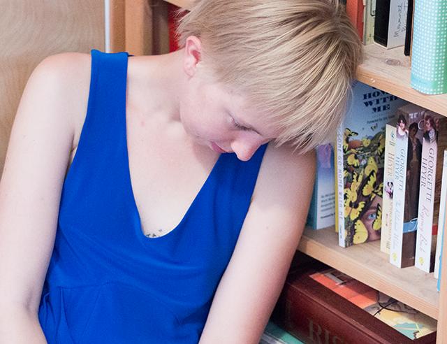 royal blue Sympli dress, short blonde hair, bookshelf