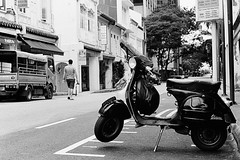 motorcycle(0.0), scooter(1.0), vehicle(1.0), mode of transport(1.0), snapshot(1.0), road(1.0), monochrome photography(1.0), monochrome(1.0), black-and-white(1.0), street(1.0), black(1.0), infrastructure(1.0), vespa(1.0),