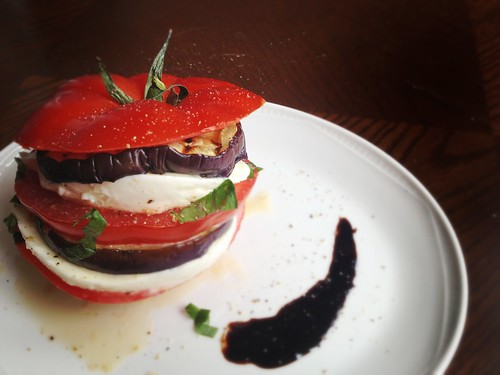 stack of grilled tomatoes, aubergines, mozarella with basil leaves and balsamic reduction