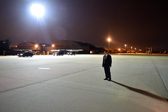 A Diplomatic Security Service agent stands watch as the motorcade carrying U.S. Secretary of State John Kerry arrives at Andrews Air Force Base in suburban Washington during the early morning hours of July 21, 2014, as the Secretary headed to Egypt in support of efforts to reach a ceasefire between Israel and Hamas amid their battle in Gaza. [State Department photo/ Public Domain]