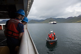 Seamen Brendan Kiley and Michael Mackie observe as a Coast Guard small boat crew passes a line to the Coast Guard Cutter Alex Haley crew from the Seattle-based fishing vessel Sea Trader during a drill near Unalaska, Alaska, Sept. 9, 2014. The small boat crew transferred the line so the Alex Haley crew could take the Sea Trader in tow. (U.S. Coast Guard photo by Petty Officer 3rd Class Dale Arnould)