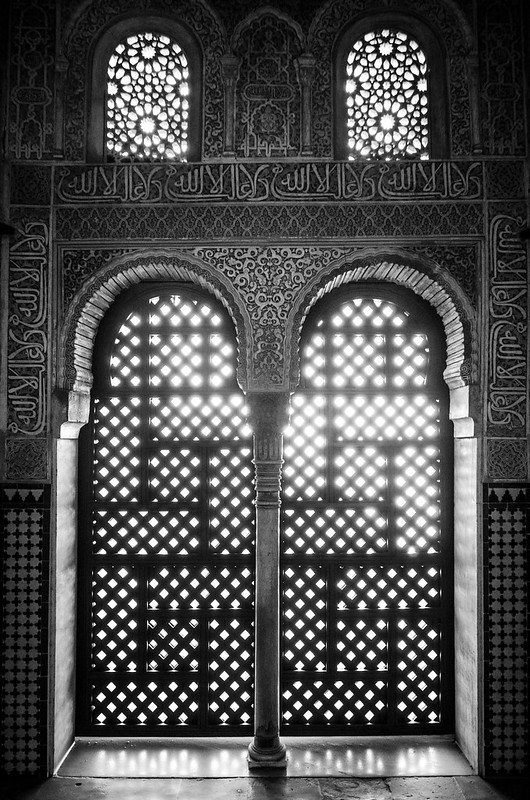 Sunlight glows through detailed Moorish carvings inside the Nasrid Palaces at the Alhambra in Granada.