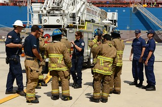 Firefighters with Chevron Fire Department prepare to respond to a simulated fire aboard a container ship as part of an oil and hazardous substance response exercise at Kalaeloa Barbers Point Harbor Sept. 10, 2014. The exercise was designed to test and evaluate core components of the Hawaii Area Contingency Plan, Chevron Facility Response Plan and various emergency response plans during a simulated fire and oil spill. (U.S. Coast Guard photo by Petty Officer 3rd Class Melissa E. McKenzie)