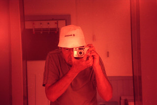 reflected self-portrait with Pentax Espio 90MC camera and Skoda hat