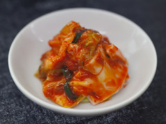 Kimchi served in white saucer as side dish