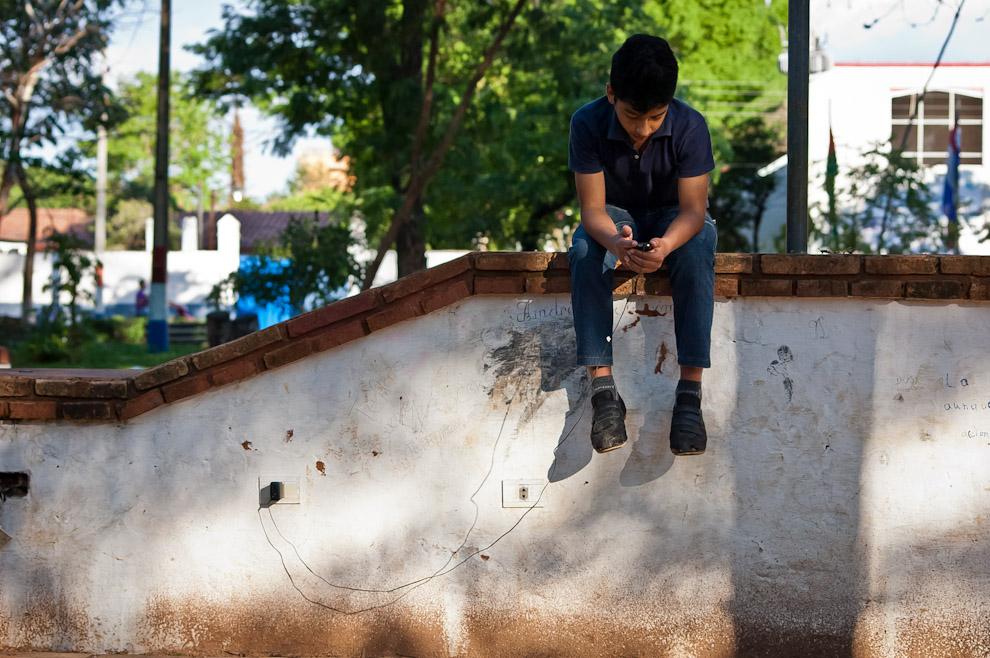 Un adolescente carga su teléfono usando la energía eléctrica de la plaza central, en la Ciudad de San Pedro de Ycuamandiyú. La plaza cuenta con energía y cobertura de señal de Internet por WIFI, otorgada por el municipio. (Elton Núñez)