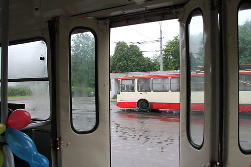 Armonikinės durys ir vaizdas į naujesnį troleibusą, kuris šiaip jau irgi yra labai senas, jeigu kalbėtumėm autobusų terminais.