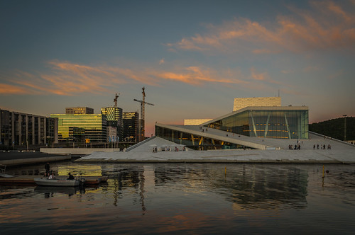 oslooperahouse opera oslo sunset water skyline hills cloud sky fjord pink orange blue crane construction high boat refelction sun summer evening scenic people outdoor architecture structure building buildings waterfront cityscape nikon d90