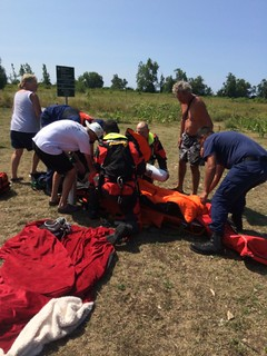 U.S. Coast Guardsmen, Canadian air crew members and volunteers attend to a woman on Main Duck Island, who was medically evacuated from a sailing vessel in Canadian waters after becoming severely ill, Aug. 10, 2014. Joint Rescue Coordination Centre Trenton, Ontario, requested the medical evacuation from the U.S. Coast Guard because they were the closest asset. U.S. Coast Guard photo by Chief Petty Officer Joshua Martin