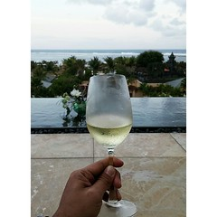 a glass of cold whine while enjoying the view from The Mulia Hotel Bali's rooftop.