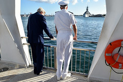 U.S. Secretary of State John Kerry and U.S. Navy Admiral Samuel Locklear, commander of the U.S. Pacific Command, stare at the U.S.S. Missouri, on which the armistice ending World War II was signed, during their visit to the memorial to the USS Arizona, which was sunk in the Pearl Harbor attack drawing the United States into the war, on August 13, 2014, after the two laid a wreath at the famed World War II site. It followed a regional military briefing coming at the conclusion of an around the world trip that included stops in Burma, Australia, and the Solomon Islands. [State Department photo/ Public Domain]