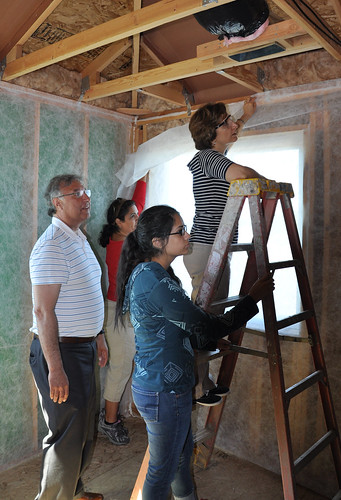 Administrator Tony Hernandez, Teresa and Andrea Hernandez, and US Representative Suzanne Bonamici prep the walls for insulation.